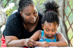 African mother supervising daughter writing.